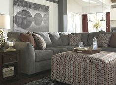 This sectional has a warm slate-hue, eye-catching accent pillows, and streamlined design, making it the perfect place to gather the family and relax in your contemporary home. Living Room Decor On A Budget, New Living Room, Living Spaces, At Home Furniture Store, Furniture Decor, Dream Decor, Apartment Living, Perfect Place, Perfect Fit