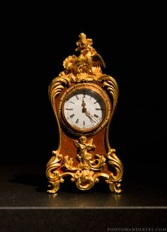 The clock in the style of a cartel, Fabergé, master Michael Perkhin, 1890.  The clock is carved from agate with gold trim.  Engraved on the reverse side, the Grand Duchess Maria Alexandrovna's monogram.