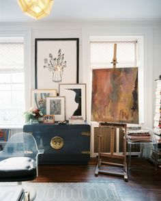 Gorgeous, bohemian living room corner featuring hardwood floors, a rustic turquoise buffet, framed artwork, an easel for canvas display and plastic seating   Photos by Patrick Cline for Lonny