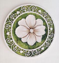 Prato com 25cm de diâmetro com arabesco branco de moldura, no centro flor branca.