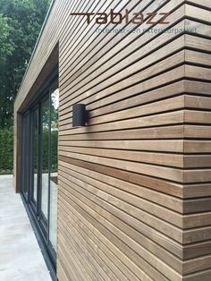 An outbuilding finished with thermo ash wood cladding and black sliding . - An outbuilding finished with thermo ash wood façade cladding and black sliding doors for optimum u -