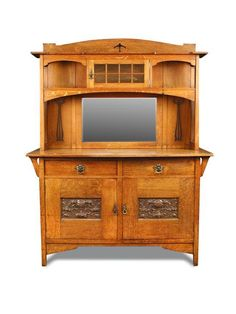 <b>Robson & Sons, Newcastle-on-Tyne, an Arts & Crafts oak dresser,</b> the top with central leaded glass cupboard flanked by arched recesses above a mirror back and pierced foliate motifs, the base with two long drawers over a pair of carved panel cupboard doors h:182 w:152 d:60 cm