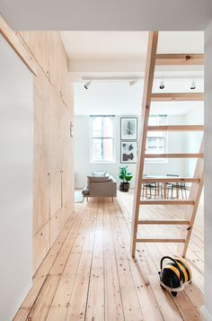 A young family of course will also want to be able to entertain on occasion and perhaps have overnight guests. The lofted area of the apartment accomplishes that goal with a spare guest bed as well as access area to hidden storage compartments. The lofted storage is actually home to more furniture, made from plywood, that folds flat to save space.