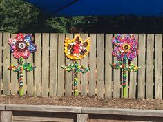 Bottle cap flower garden at primary school. Marine ply painted flowers with bottle caps attached. Bottle caps were glued but students but then had a small screw place through each one so they would hold up in weather.