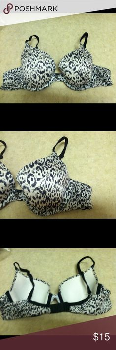 Victorias Secret Lined Demi Bra This ivory bra has black print on the cups & sides, adjustable black straps, underwire, a charm in the middle, & tiny shiny studs on both cups.  It has a 2 hook closure & is 65% Nylon/35% Elastane. Victoria's Secret Intimates & Sleepwear Bras