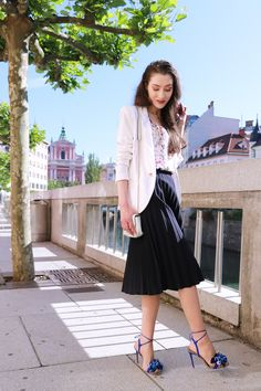 Fashion blogger Veronika Lipar of Brunette From Wall Street in Ljubljana wearing black vintage midi plissé skirt, blue Tropicana tasseled beaded sandals from Aquazzura, floral top, and white blazer for a chic summer look