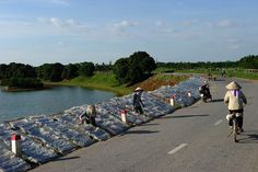 This picture taken on August 20, 2015 shows farmers drying vermicelli along a road in the outskirts of Hanoi. Experts have worried that climate change will hurt many poor people in Vietnam. Photo: AFP