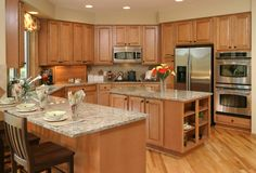 A U-shaped kitchen features light wood cabinetry and granite countertops.