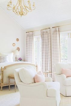 White and pink French bedroom features a high vaulted ceiling accented with a gold chandelier illuminating a French bed with headboard and footboard next to a wall of windows dressed in pink plaid curtains.