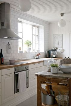 white subway tile + woodtop counters + globe pendants + old harvest table-island