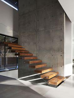 Escada de Madeira e Vidro e Parede de Concreto. Arquiteto: Pitsou Kedem Architects. Fotógrafo: Amit Geron.