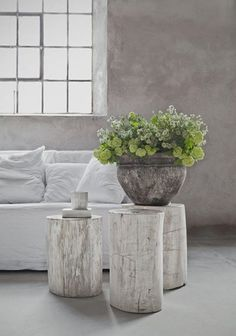 curioussofa.com  There are so many things that are right about this setting; the plaster walls, the deep window sill, the iron window panes, the white linen slipcovered sofa, the giant urn with freshly picked garden flowers but of course I love the giant wood stumps; white ashed or natural, used in a grouping as side tables.