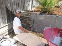 covering cement blocks with rock facing.  The best way to dress up that oh so important retaining wall!
