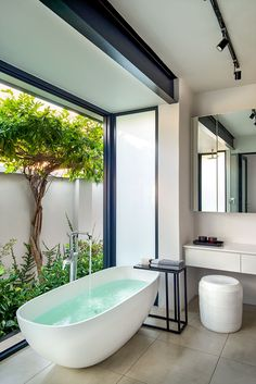 The new main bathroom is a locus of calm, with doors that fold away to reveal a secluded garden. The freestanding bath is from Dado Baths, and it's matched with an old side table of Hendrien's and a white ceramic stool by Anthony Shapiro. Outdoor Bathrooms, Dream Bathrooms, Beautiful Bathrooms, Modern Bathroom, Outdoor Baths, Bath Window, Interior Minimalista, Bathroom Interior Design, Interior Garden