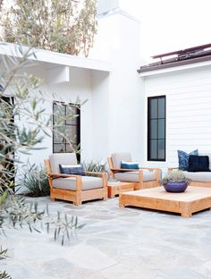 Outdoor wooden chairs with grey cushions and blue throw pillows, and wooden coffee table