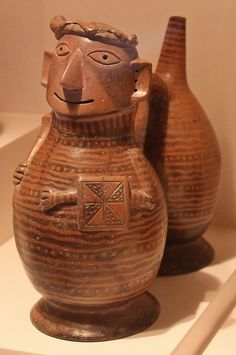 Virú Culture double-chambered sculpted bottle  *   Formative Period (1250 BC - 1 AD). *  Virú-Gallinazo Culture double-chambered sculpted bottle representing a warrior with headdress and face paint holding a baton and a square shield with geometric decorations.