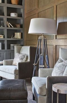 Masculine den features a chic tripod floor lamp placed on a gray rug between gray velvet wingback chairs positioned in front of a brown oak wainscoted wall and paired with brown leather ottomans.