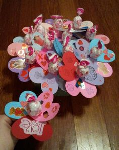 Valentines my children and I made for daycare and kindergarten class. We traced hearts on different color card stock sheets ($.44 ea) then decorated with stamps ($.99 for 3 pack at walmart) and stickers ($.99 to $3.00 depending on what you want) then punched a hole in the bottum of 3 and put a sucker (blow ups $2.50 walmart for box of 24) through the holes and hot glued the underneath so they wouldnt fall off! I also bought a foam circle from hobby lobby and stuck the flowers into to hold…