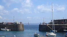 Tightrope walking across Mousehole harbour entrance, Cornwall.
