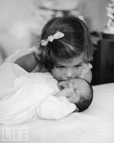 Three-year-old Caroline Kennedy kisses her baby brother John at the White House, February 1961