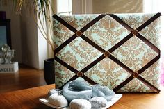 Create your own memory board using basic upholstery skills. Perfect to hold great holiday memories! Things you will need: Wooden board Fabric Polyester batting Staple gun Ribbon Scissors Ruler and marker Instructions: Lay out your po. Writing Portfolio, Ribbon Crafts, Create Your Own, Upholstery, Layout, Throw Pillows, Memories, Blanket, Handmade Gifts