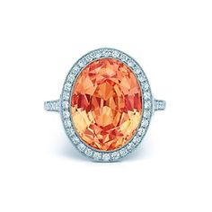 Orange sapphire and diamond ring in platinum.