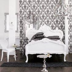 Chambre baroque toute en noir et blanc : le mobilier tout blanc, est en contraste avec le papier peint côté lit, et le tapis et linge de lit noir