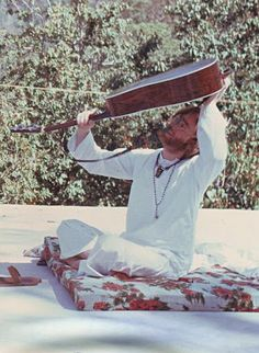 John Lennon attempting to retrieve his guitar pick while in India, 1968
