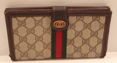 "This vintage Gucci clutch wallet has the brown ""G"" with the green and red racer stripe and gold GG emblem.  It has detailed in brown leather, holds up to 9 credit cards and has an ID holder.  There is a checkbook area with a brown leather folding cover and an area to hold a passport.  On the back of the wallet is a snap-closure coin purse.  This wallet has some slight wear around the fold, but otherwise is in great condition.     www.handbagconsignmentshop.com"
