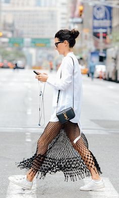 White button down over a black fringe skirt, YSL crossbody and white sneakers