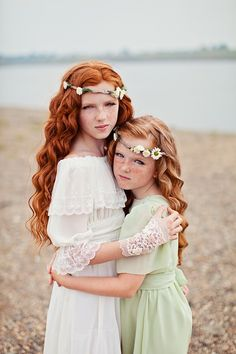 Two girls long curly red hair hugging sisters serious morose