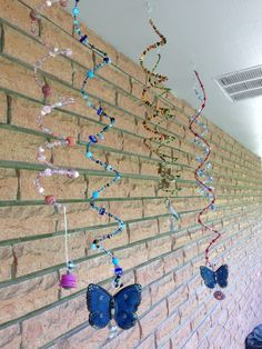 Memory wire and beads with something heavy on the end. I used old brooches, clay butterflies and painted washers. I hung them under the soffit on the patio so they won't get too much weather.  I had everything on hand so no expense in this project for me. Not fine art or anything but an inexpensive way to dress up your outdoor space!