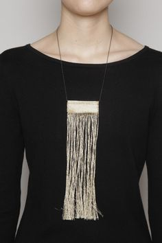 justine ashbee / fw12 / tapestry-necklace - Hand woven necklace of gold metallic and black cotton thread with long fringe hanging from brass bar.