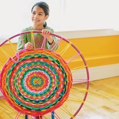 """Hula Hoop Rug. Love this. I happen to have a couple of spare hoola hoops that """"don't work"""" anymore - ha. Great group project. Kids could add to it when they're finished with their work."""