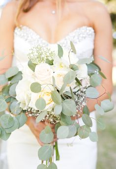 Bouquet of white roses surrounded by eucalyptus leaves and baby's breath // Kristen Hammonds Photography