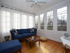 Enclosed porch with windows and white drapes