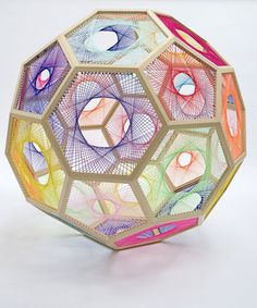 Snap, snap, snap, snap…five, six, seven, eight. Presenting a mathematic beat featuring threads bound into beautiful bursts by Nike Savvas. A collaboration of wooden outlined hexagons create a unique take on the soccer ball pleasing in pink, yellow, teal, and other shades from the Caribbean skyline.Various skeletons offer new formulas, fanning out colors to chase …