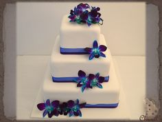 3 Tier Square Wedding Cake 5, 8 & 11 Inch. Covered in White fondant and decorated with fresh Singapore orchids in a light wrapping cascade effect with Blue & Purple coloured organza & thin Satin ribbons around the base of each tier.