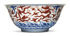 A RARE AND LARGE IRON-RED AND BLUE 'DRAGON' BOWL JIAJING MARK AND PERIOD the deep rounded sides rising from a short straight foot to an everted rim, painted to the interior with a medallion enclosing an iron-red dragon chasing a flaming pearl above rich cobalt-blue foaming waves, the exterior with eight similar dragons chasing flaming pearls amidst ruyi clouds and fire scrolls and above foaming waves, the base inscribed in underglaze-blue with the six-character mark within a double circle