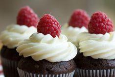Cupcakes mit Frosting und Himbeeren