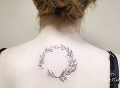 Floral wreath tattoo on the upper back.