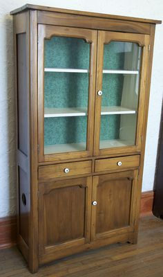 This is a beautiful kitchen cabinet from the 1910's. It is in very good condition. There are three shelves on the upper portion with glass doors to display the items within. The lower portion is the pie safe area that has circular cut outs on the sides and a shelf in the interior.  Height: 71 3/4 inches Width: 39 1/2 inches Depth: 15 1/2 inches