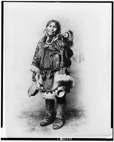 Eskimo mother dressed in fur clothing with baby on her back, ca1903