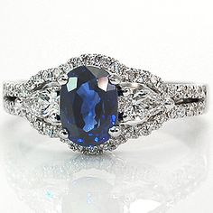 Venus from Knox Jewelers is a unique twist on a three stone ring. This ring is currently shown with a 1.00ct cushion cut blue sapphire center stone and two pear shaped diamonds to either side. These three center stones are outlined by a halo of micro pave stones that then form into a double line of side stones on the band.