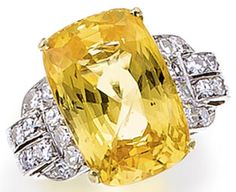 A Yellow Sapphire and Diamond Ring set with a cushion-shaped yellow sapphire weighing 19.01 carats, flanked by arched shoulders set with single-cut diamonds, mounted in platinum and 18K gold.  Via Bonhams.