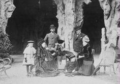 Photograph of Queen Victoria (1819-1910) on holiday with Princess Beatrice (1857–1944); Princesses Margaret (1882-1920) and Patricia of Connaught (1886-1974) ; Prince Henry of Battenberg (1886-1974); Prince Arthur of Connaught (1883-1938); and the Marquis of Lorne (1845-1914), dressed in outdoor clothing sitting in front of what look like cave entrances