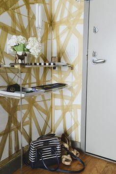Contemporary foyer features walls painted in white and gold lined with a brass and lucite console table with shelf.