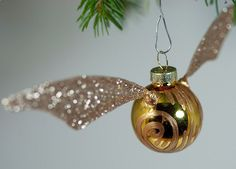 Create these Golden Snitch Ornaments for Christmas, by adding some craft wire to shape your snitch wings.