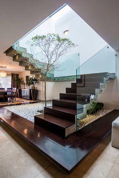 Escada com laterais de vidro montada ao redor do jardim de inverno. #escada