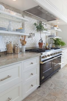 Stunning kitchen features white shaker cabinets paired with brushed nickel hardware alongside gray counters and a beveled mini subway tile backsplash trimmed with gray stone which highlights a Viking Range in Black situated below a swing arm pot filler and below a paneled vent hood with floating shelves on either side.